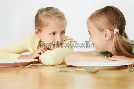 two girls leaning on table with