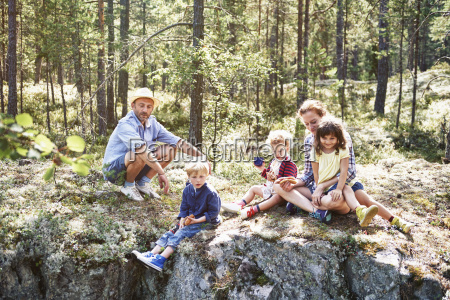 family sitting on rocks in forest