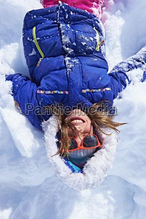 girl lying down in snow chamonix