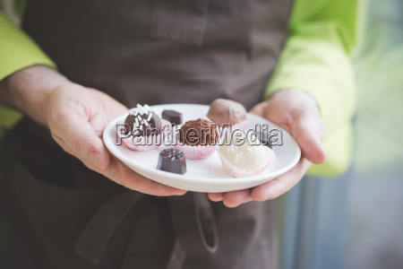 waiter carrying plate of varying confectionery
