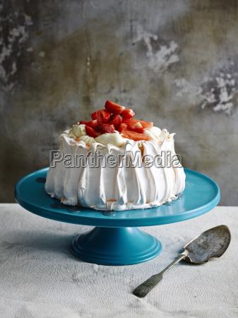 strawberry covered pavlova on blue ceramic