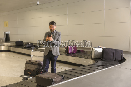 man waiting for luggage at