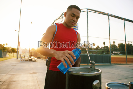 young man filling water bottle from