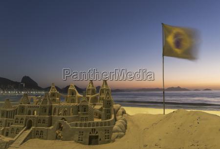 sandcastle and brazilian flag on copacabana