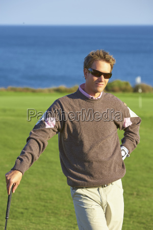 golfer wearing sunglasses leaning against golf