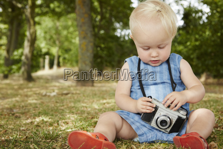 baby girl sitting on grass holding