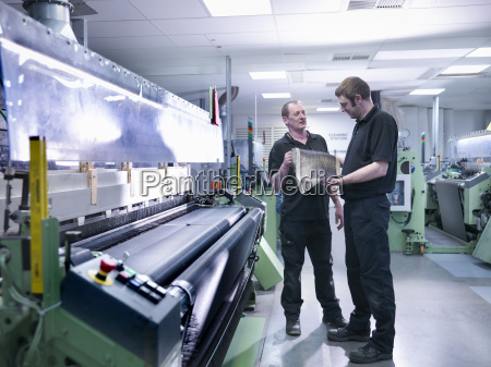 workers inspecting carbon fibre sample in