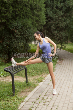 young female runner stretching legs on