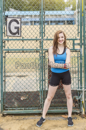 young woman standing beside sports ground
