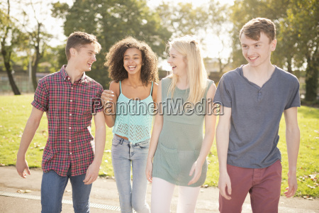 four young adult friends strolling in