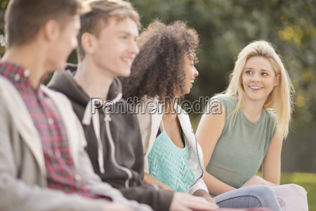 four young adult friends talking in