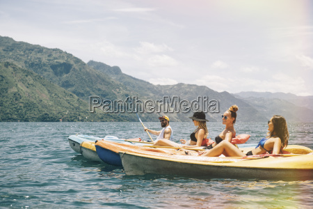 four young adult friends kayaking on