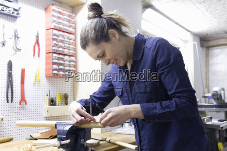 young female carpenter measuring timber in