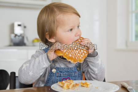 cute female toddler eating cake at