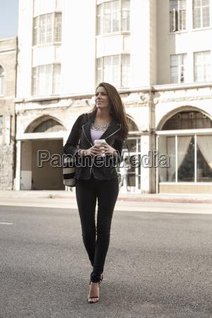 woman walking in street holding coffee
