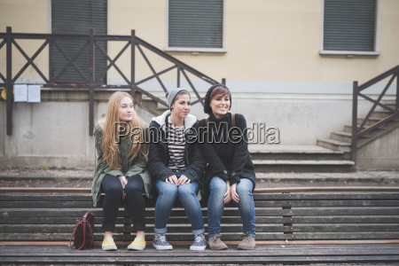 three sisters sitting on park bench