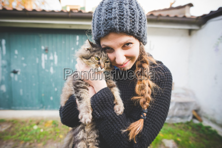 young woman wearing knit hat snuggling