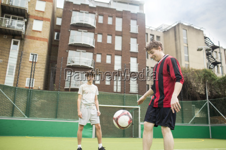two young men playing football on