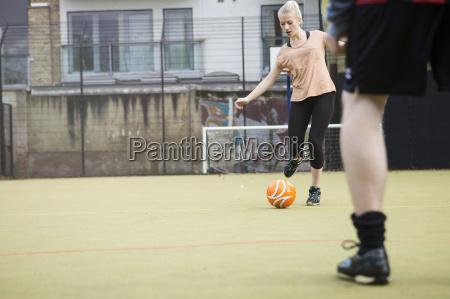 young woman playing football on urban
