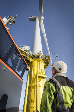 engineers climbing wind turbine from boat