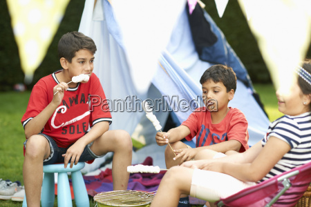 girl and brothers eating toasted marshmallows