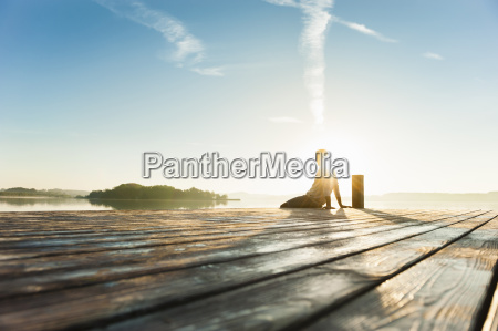 young man sitting on pier of