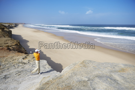 golfer standing on cliff overlooking beach