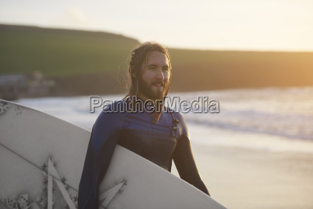 portrait of young male surfer carrying
