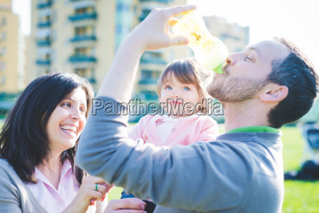 mid adult man drinking toddler daughters