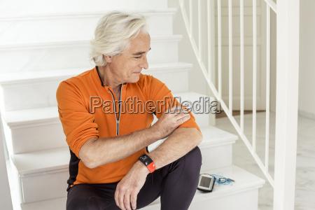 senior man sitting on staircase preparing