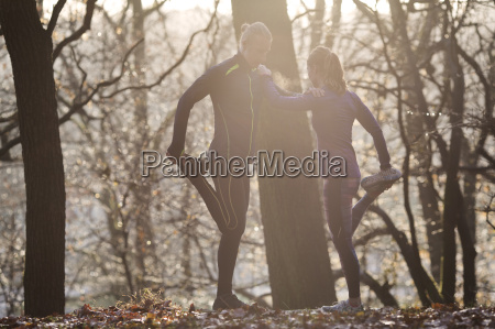 couple in forest leaning against each
