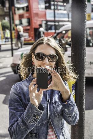 mid adult woman wearing sunglasses taking