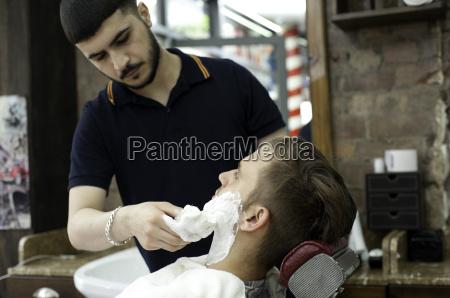 young man in barbershop applying shaving