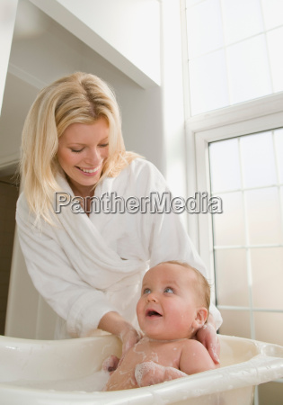 a mother bathing her baby boy