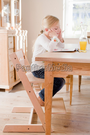 girl sitting at table reading