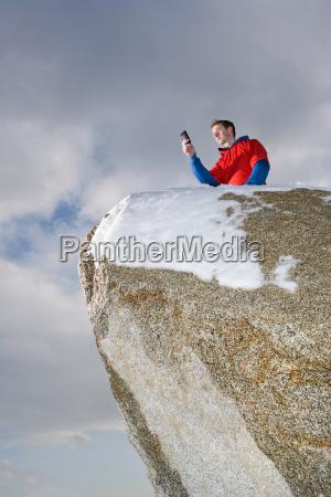 climber taking picture on mountain peak