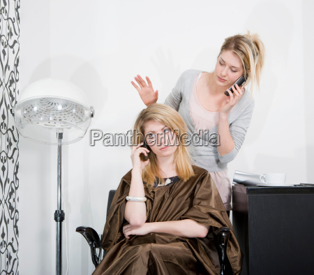 woman and hair stylist on phones