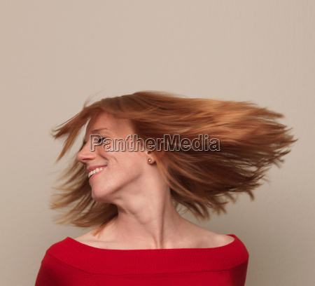 woman spinning head around hair flying