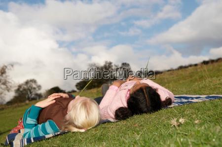 two girls lying on hillside