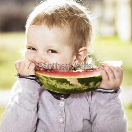 toddler girl eating watermelon outdoors