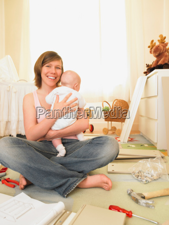 woman with baby building furniture