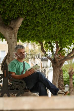 man sitting on bench reading guidebook