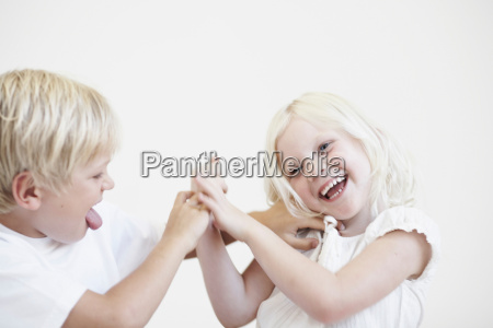 young boy tickling young girl