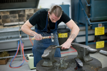 man using hammer for metalworking in