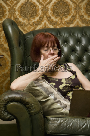 mature lady yawning whilst reading at