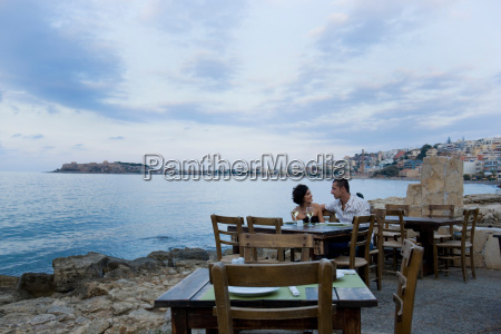 couple sitting at waterfront cafe