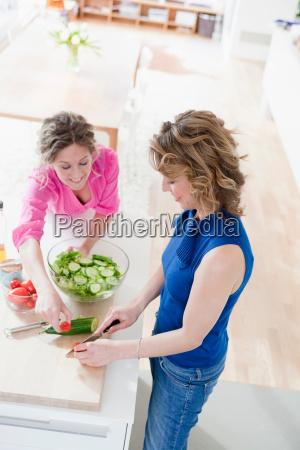 two woman preparing salad in kitchen
