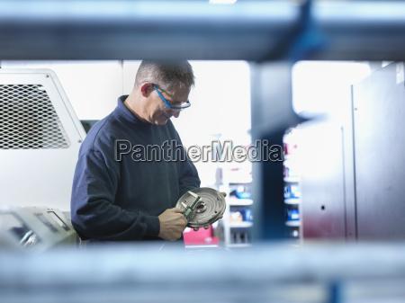 engineer measuring metal part in factory