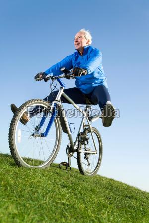 senior man riding mountain bike