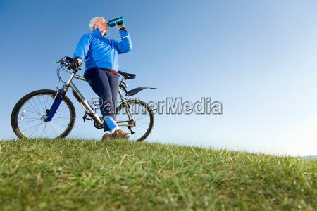 senior man drinking water on bike
